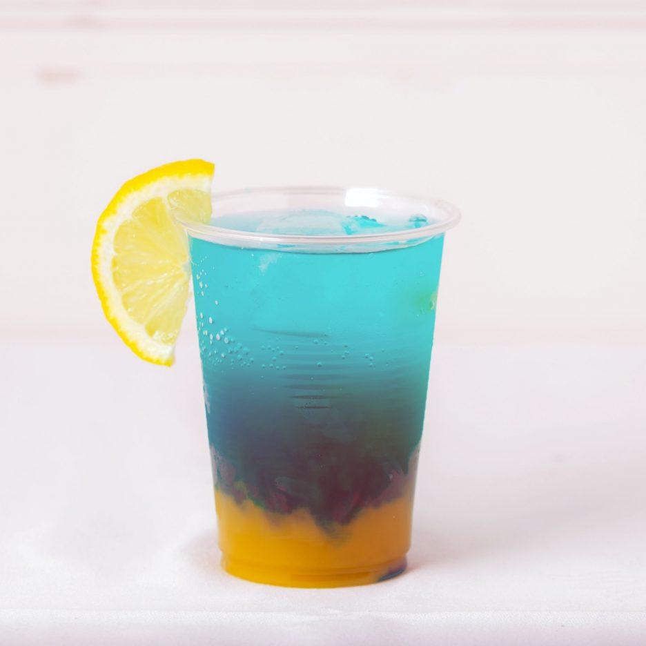 松山会場-12 matsuyama   焼酎甲類をグラス1/3程度注ぐ 氷を2~3個入れる マンゴージュースを適量注ぐ、 ブルーキュラソーを1/3程度注ぐ、 ソーダで満たし、 レモンを浮かべて出来上がり    焼酎:グランブルー マンゴージュース ブルーキュラソー ソーダ レモン